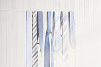 Neckties hanging on clothesline against wooden wall