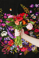 Cropped image of woman holding bunch of roses against designed fabric