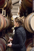 Woman holding wineglass while standing in wine cellar
