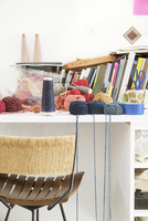 Various threads, yarns and books on table by chair against wall at home