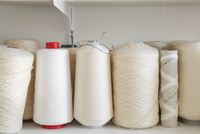 Close-up of white spools on shelf at home studio