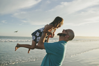 Happy father lifting daughter at beach during sunset
