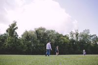 Happy parents playing with son on field against sky