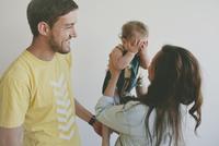 Man looking at woman lifting baby girl at home