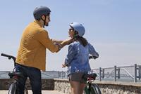 Rear view of man assisting woman in wearing bicycle helmet on promenade