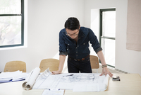 Businessman analyzing blueprint at desk in creative office