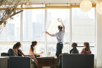 Businessman holding blueprint against window during meeting