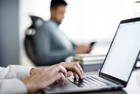 Cropped image of businessman using laptop in creative office