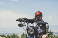 Portrait of biker sitting on cruiser motorcycle against sky