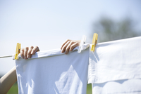 Close-up of woman drying clothes on clothesline 11100045871| 写真素材・ストックフォト・画像・イラスト素材|アマナイメージズ
