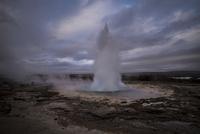 Geyser erupting hot spring against cloudy sky
