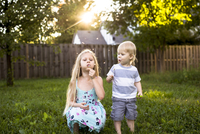 Playful siblings blowing dandelion in backyard