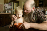Father feeding soup to son at dinning table
