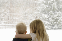 Rear view of siblings looking through window during winter