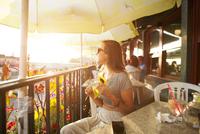 Woman in sunglasses holding sunflower in cafe 11100046596| 写真素材・ストックフォト・画像・イラスト素材|アマナイメージズ