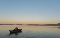 High angle view of man in boat on lake against clear sky during sunset
