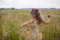 Girl with arms outstretched playing on grassy field 11100046736| 写真素材・ストックフォト・画像・イラスト素材|アマナイメージズ