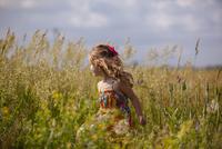 Happy girl walking amidst plants on grassy field