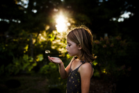 Side view of girl blowing dandelion seed while standing at yard 11100046748| 写真素材・ストックフォト・画像・イラスト素材|アマナイメージズ