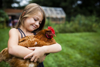 Smiling girl holding hen while standing in yard