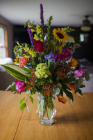 Various flowers in glass vase on wooden table at home