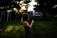 Side view of girl holding dandelion seed while standing at yard