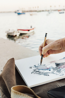 Cropped image of woman painting on paper with boats moored at sea 11100046794| 写真素材・ストックフォト・画像・イラスト素材|アマナイメージズ