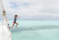 Full length of girl diving in sea from boat against cloudy sky