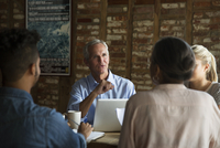 Confident businessman talking to colleagues during meeting at cafe