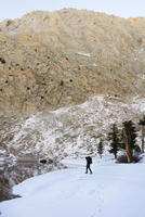 Hiker walking on snow covered field by lake against mountain