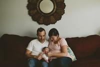 Mother and father carrying baby girl while sitting on sofa at home 11100047061| 写真素材・ストックフォト・画像・イラスト素材|アマナイメージズ