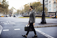 Side view of businessman crossing road in city