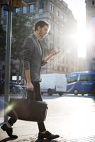 Man using mobile phone while walking on city street 11100047102| 写真素材・ストックフォト・画像・イラスト素材|アマナイメージズ