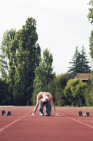 Athlete poised at starting block on track