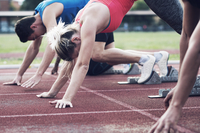 Athletes poised at starting blocks on track
