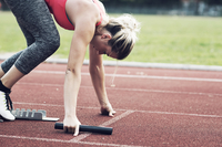 Athlete with relay baton poised at starting block on track