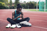 Athlete using mobile phone while sitting on track