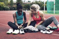 Athlete friends looking at mobile phone while sitting on track