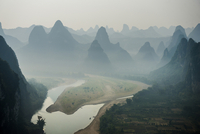 River flowing against mountain during foggy weather