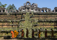 Monks walking by Angkor Wat on sunny day