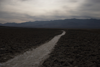 Pathway amidst Death Valley National Park against cloudy sky