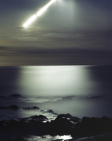 Long exposure of moon shining over rocks in sea