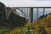 Arch bridge over mountains by sea