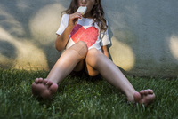 Girl eating ice cream while sitting on grassy field against wall in yard