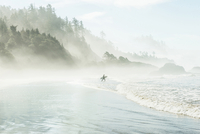 Man with surfboard walking towards sea by mountain during foggy weather