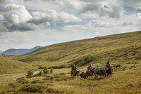 Men riding horses on hill against cloudy sky