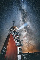 Low angle view of light emitting through lighthouse against starry sky