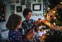 Siblings decorating Christmas tree at home 11100048093| 写真素材・ストックフォト・画像・イラスト素材|アマナイメージズ