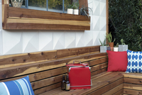 Beer bottles and cooler on wooden bench in backyard