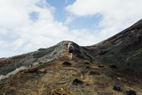 Low angle view of hiker climbing mountain against sky